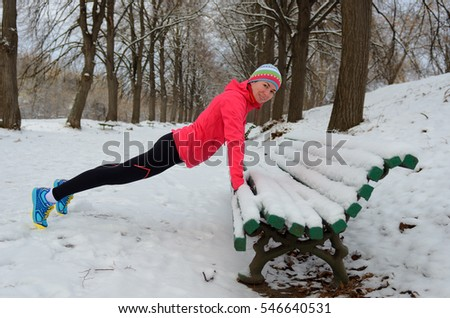 Winter fitness and running in park: happy woman runner warming up and exercising before jogging in snow, outdoor sport