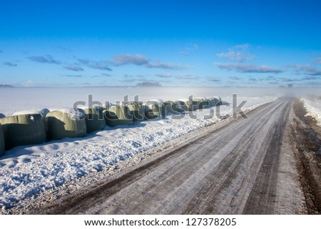 Winter foggy road with blue sky - stock photo