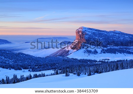 Winter forest and Mont Granier in French Alps during a colorful sunset. - stock photo