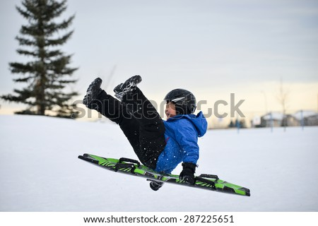Winter Fun - Child Sledding/Toboganing Fast Over Snow Ramp