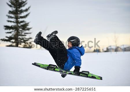 Winter Fun - Child Sledding/Toboganing Fast Over Snow Ramp - stock photo