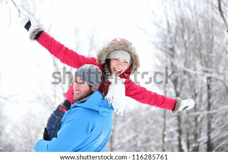 Winter fun couple playful together during winter holidays vacation outside in snow forest. Happy young interracial couple, Asian woman, Caucasian man. - stock photo