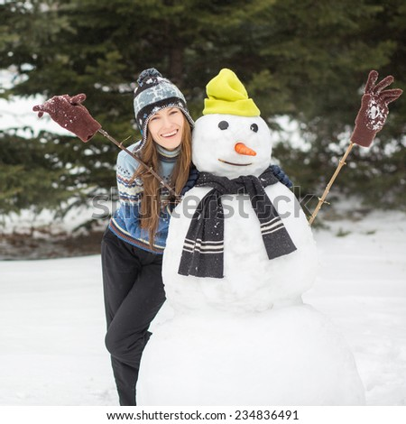 Winter fun, happy young woman making snowman. focus on woman - stock photo