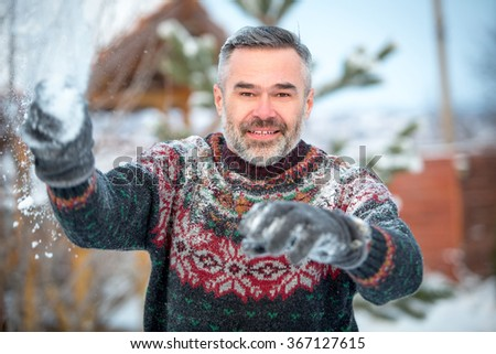Winter fun man happy smiling and throwing snowballs - stock photo