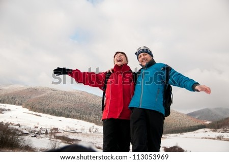 Winter fun - senior retired couple in snow - stock photo