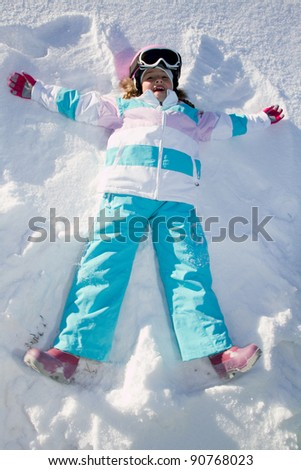 Winter fun - Snow Angel - little girl playing in snow - stock photo