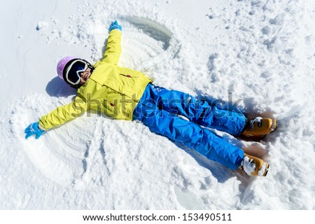 Winter fun - Snow Angel - young skier  girl playing in snow - stock photo