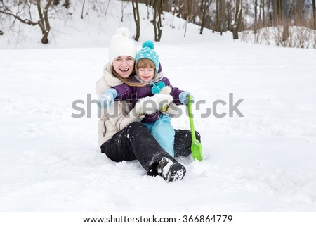 Winter fun, snow, happy children at winter time. Mother and son enjoying beautiful winter day outdoors. Happy mother and baby daughter playing with snow. family - stock photo