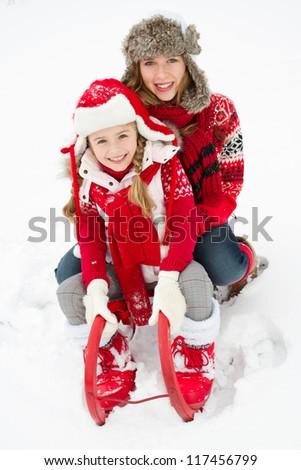 Winter, fun, snow - happy girls sledding at winter time - stock photo