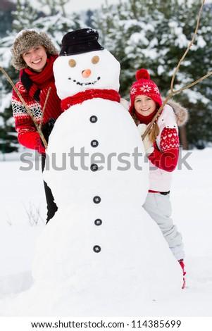 Winter fun, snowman and happy family - stock photo