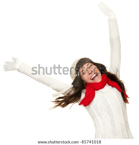 Winter fun woman winner and success concept. Cheering happy ecstatic female model with arms up celebrating winning something. Multicultural Caucasian Asian winter girl isolated on white background. - stock photo
