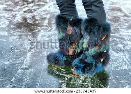 winter fur colored boots on the ice surface - stock photo