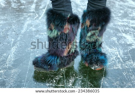 winter furry shoes on the ice surface - stock photo