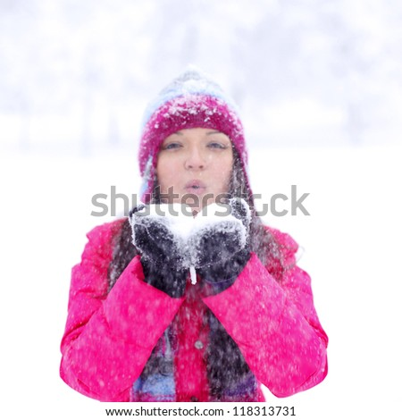 winter girl blow on snow in hands - stock photo