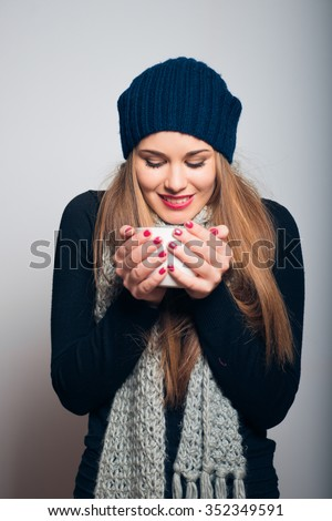 Winter girl drinking tea or coffee to warm up. Lifestyle studio photo isolated portrait of a woman on a gray background. - stock photo