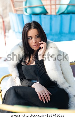 Winter Girl in Luxury Fur Coat on mobile phone - stock photo
