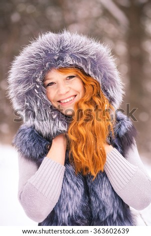 Winter girl. Portrait of beautiful young girl dressed in fur coat. Winter background. Beauty woman having fun outside on winter snowy day. Close up of female smiling face with gorgeous long red hair  - stock photo
