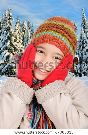 Winter happiness, adorable little girl with winter clothes between the trees in forest, snow around