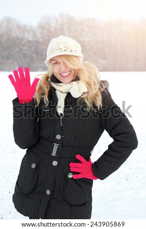 winter happy woman in snow looking up at camera and waving outside on snowing sunny cold winter day. Portrait Caucasian smiling female model with pink gloves in first snow - stock photo