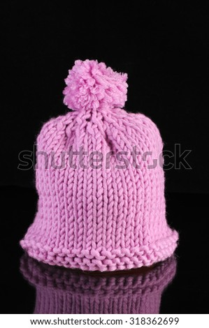Winter hat isolated on black background with reflection - stock photo