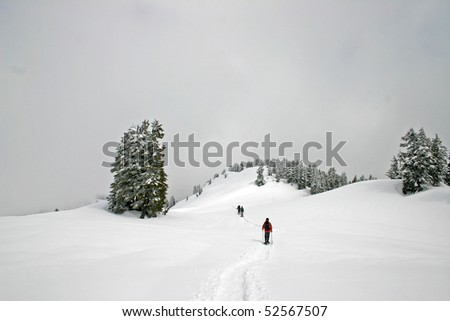 Winter hiking view while hikers cross snow mountain field.