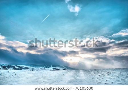 Winter hills covered by snow against sunset