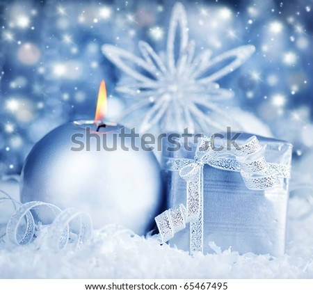 Winter holiday background with silver present gift box, candle ornament & Christmas snow decoration - stock photo