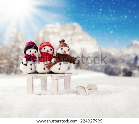 Winter holiday happy snow men with blur landscape on background. Concept love and togetherness - stock photo