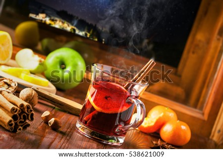 Winter holiday hot alcohol drink on a table. Mulled wine with fruits and spices by window, winter landscape with sky full of stars on background.