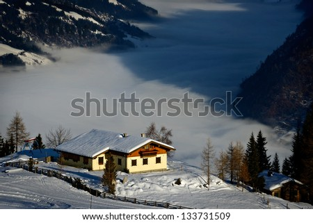 Winter holiday house in rising sun beams in the Alps in winter - stock photo