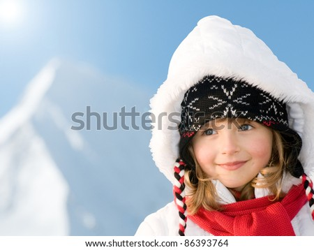 Winter holiday - portrait of cute girl, snowy mountains in background - stock photo