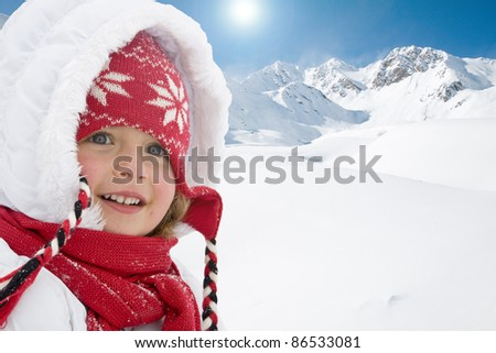Winter holiday - portrait of cute girl, snowy mountains in background (space for text) - stock photo