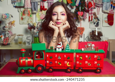 Winter holidays celebration concept. Portrait of doll like brunette posing with wooden handmade train in vintage restaurant, cafe. Homemade christmas decoration. Close up. Retro style. Indoor shot - stock photo