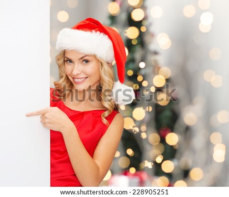 winter holidays, christmas, advertising and people concept - smiling young woman in santa helper hat with white blank billboard over tree lights background - stock photo