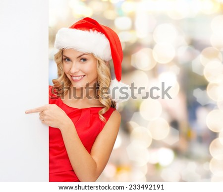 winter holidays, christmas, advertising and people concept - smiling young woman in santa helper hat with white blank billboard over lights background - stock photo