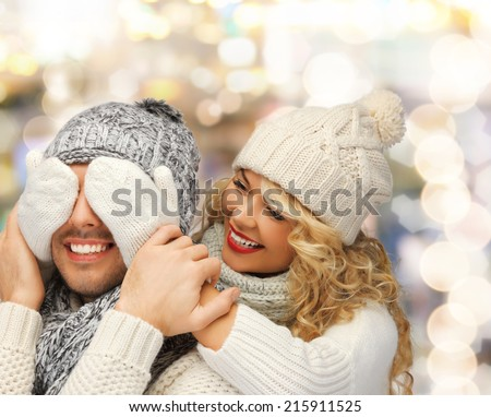winter, holidays, christmas and people concept - smiling couple in sweaters and santa helper hats over lights background - stock photo