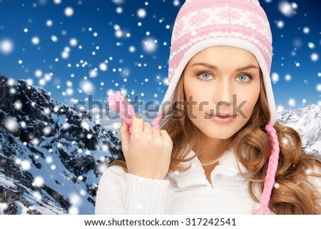 winter holidays, christmas, fashion and people concept - happy young woman in winter hat over snow and mountains background