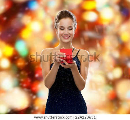 winter holidays, christmas, presents, luxury and people concept - smiling woman in dress holding red gift box over red lights background - stock photo