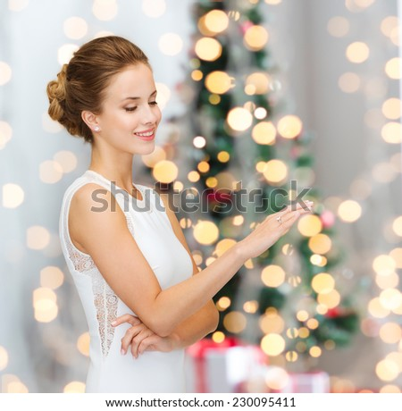 winter holidays, presents and people concept - smiling woman in white dress wearing diamond ring over blue over christmas tree lights background - stock photo