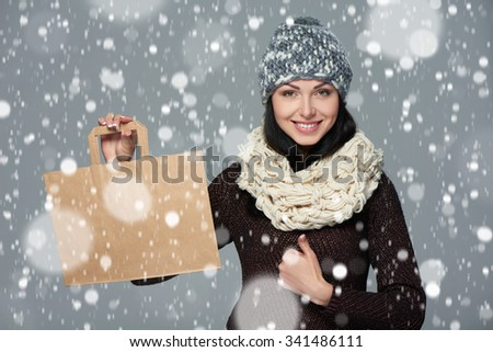 Winter holidays sale, shopping, Christmas concept. Portrait of smiling woman wearing warm winter hat and muffler showing shopping bag with empty copy space and gesturing thumb up over snow background - stock photo