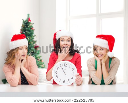 winter, holidays, time and people concept - smiling women in santa helper hats with clock over living room and christmas tree background - stock photo