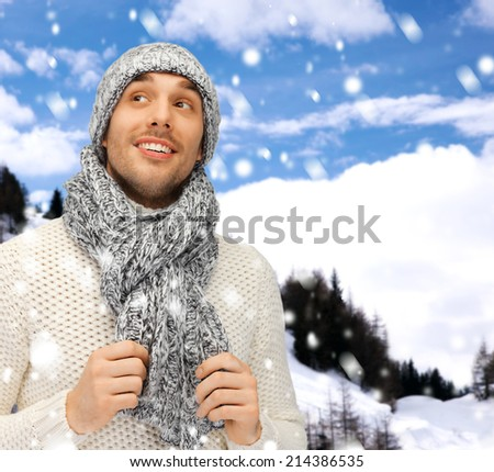 winter holidays, vacation and lifestyle concept - handsome man in warm sweater, hat and scarf
