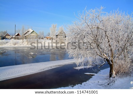 winter ice on river near villages - stock photo