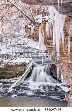 Winter icicles hang from the canyon walls at Owen County, Indiana's McCormick's Creek State Park. - stock photo