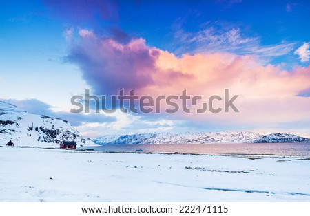Winter in Norway - Sunset in mountains with red house and the ocean. Panorama - stock photo