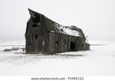WInter in Palouse snow all around this old barn that is ready to collapse. - stock photo