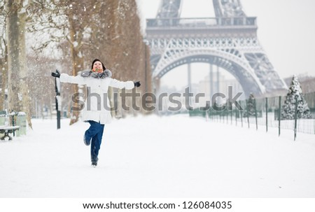 Winter in Paris. Happy young girl jumping - stock photo