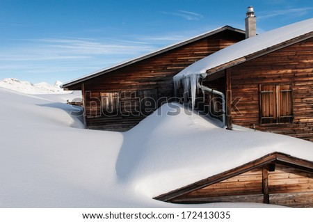 winter in Switzerland with snow covered mountains. House covered with snow. Beautiful  house. Romantic holiday house. Apartment. Home sweet home. House at mountain top. - stock photo
