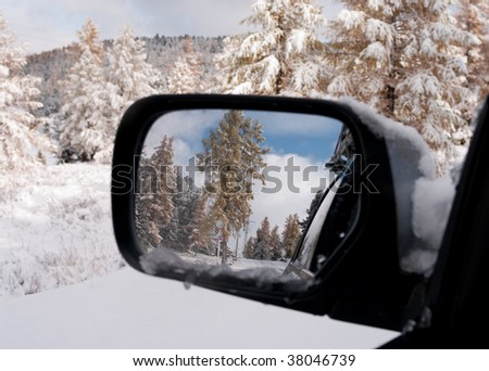 Winter in the rear-view mirror of auto. - stock photo