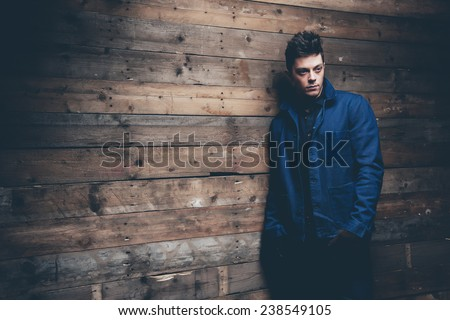 Winter jeans fashion man with short dark hair. Wearing blue jeans, jacket and brown leather gloves. Leaning against old wooden wall. - stock photo